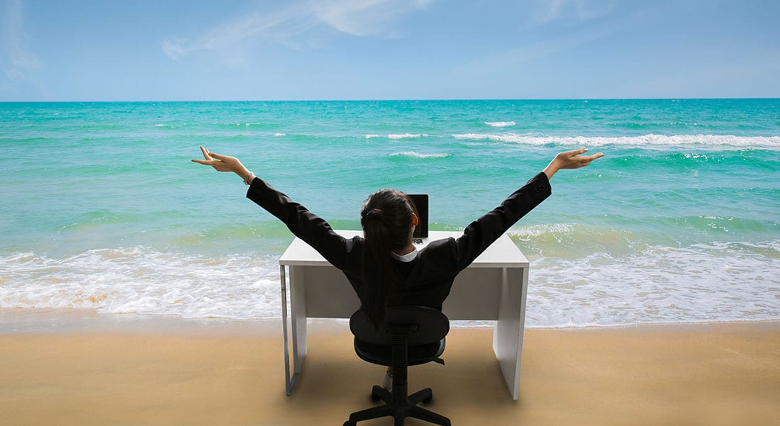 Woman sitting at office desk on the beach