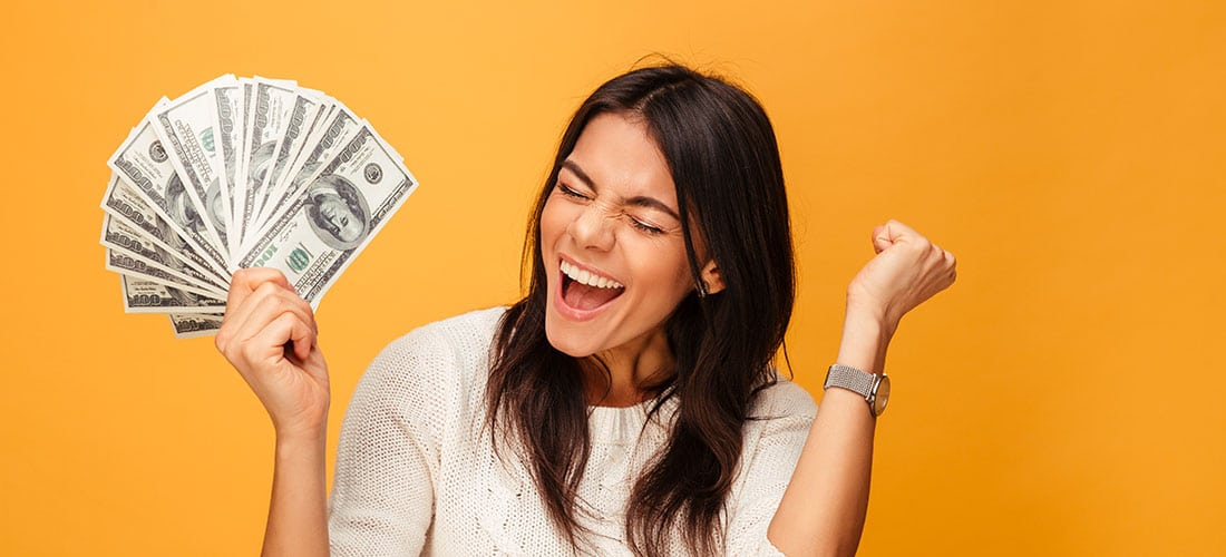 Woman cheering with handful of money